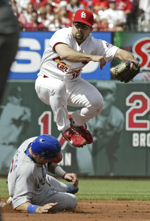 The St. Louis Cardinals' Aaron Miles, top, leaps over the Chicago Cubs' Mark DeRos after making the out in the second inning of their game in St. Loui...