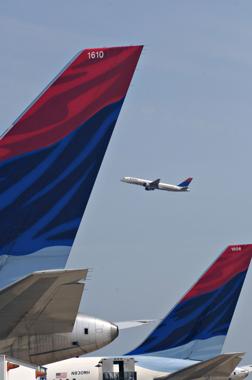 A Delta Air Lines jet, framed by the tail sections of two other Delta jets parked at a gate, takes off from Hartsfield Jackson International Airport i...