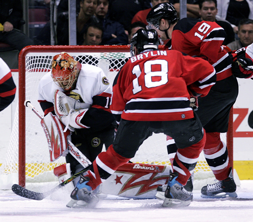 Ottawa Senators goalie Ray Emery, left, grabs the puck as the New Jersey Devils' Sergei Brylin, center, and Travis Zajac pressure him during first-per...