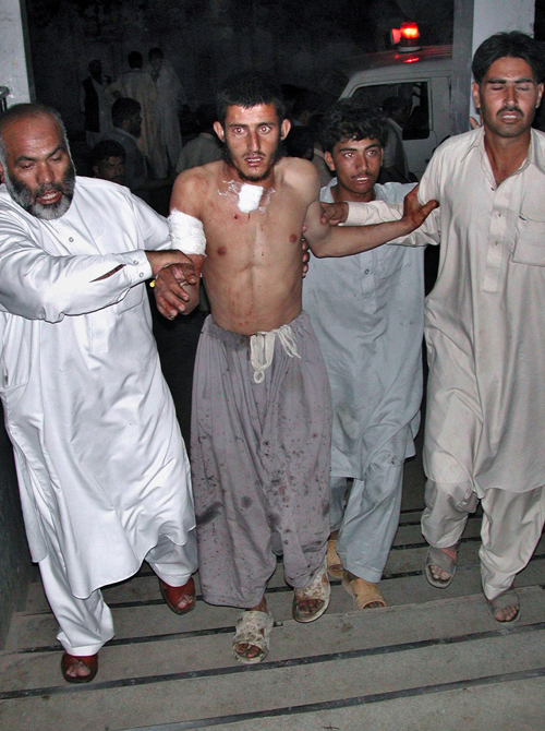 Pakistani volunteers bring an injured victim of suicide bombing to hospital for treatment in Peshawar, Pakistan on Saturday.
