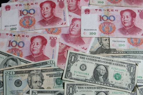 Chinese yuan notes and U.S. dollar bills are photographed in this file photo. Beijing has ordered banks to set aside more money as reserves for the se...