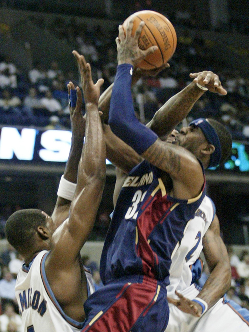 Larry Hughes, center, of the Cleveland Cavaliers gets fouled by the Washington Wizards' DeShawn Stevenson (behind Hughes) while trying to put up a sho...