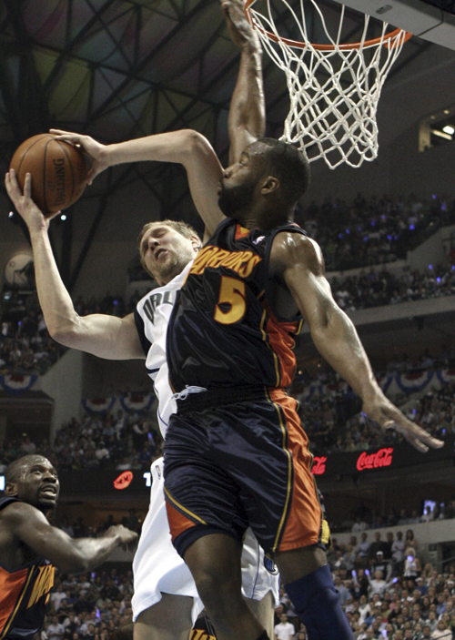 The Dallas Mavericks' Dirk Nowitzki, left, of Germany, goes to the basket as The Golden State Warriors' Baron Davis (5) defends during the first half ...