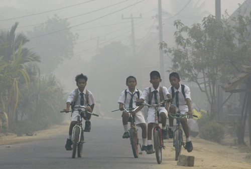 Students cycle through the haze-blanketed district of Kayu Agung, Indonesia in this October 16, 2006 file photo. The clouds of pollution that waft ove...