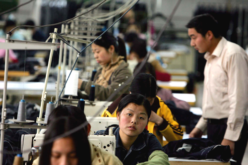 Chinese workers toil in a garment factory in Beijing in this file photo. With a critical round of trade talks with Washington opening on Wednesday, Ch...