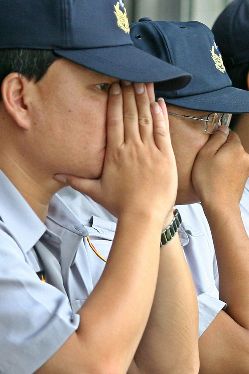 Police officers cover their noses against the stink of rotten eggs and pig dung 