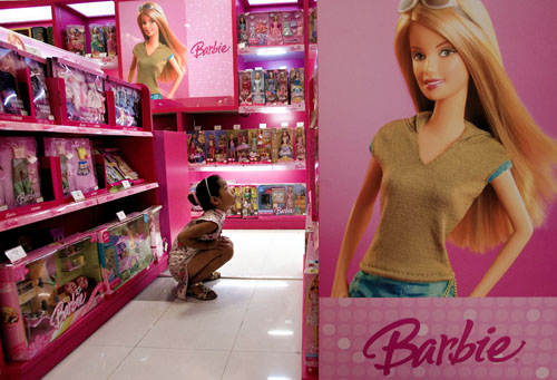 A Chinese girl looks at the Barbie dolls on display for sale at a department store in Beijing, China yesterday.
