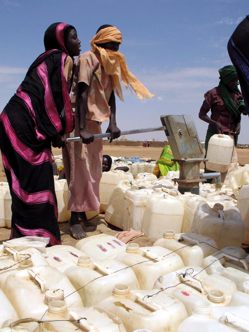 Two girls pump water into cans in Abu Shouk, Sudan, in June. Scarcity of water is a cause of the conflict that began in the Darfu region of Sudan in 2...