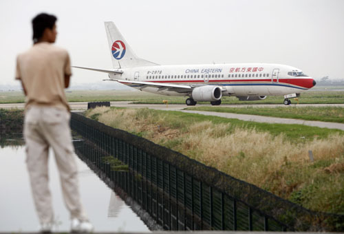 A man watches a China Eastern Airlines plane taxi down a runway at Hongqiao Airport in Shanghai, China in May.