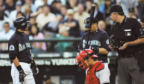 The Seattle Mariners' Ichiro Suzuki, let, stays at the plate to protest as home-plate umpire Gary Darling and Los Angeles Angels catcher Jeff Mathis l...
