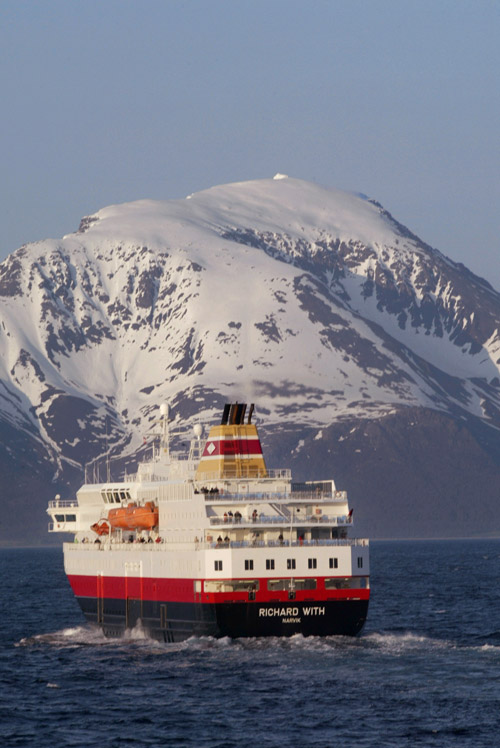 """Crossing an open stretch of sea between Skjervoy and Tromso the northbound """"Richard With"""" steams below mammoth,  snow-covered peaks along the norther..."""