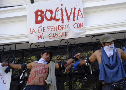 Students stand tied to railings during a protest in Sucre, Bolivia on Tuesday.