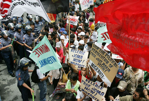 Riot police try to clear a portion of the street as militant youths hold a rally at the country's financial district of Makati city east of Manila, Ph...