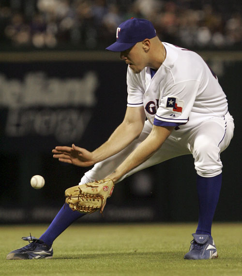 Texas Rangers starting pitcher Kameron Loe fields a ball hit by Chicago White Sox's Juan Uribe in the fourth inning of a baseball game in Arlington, T...