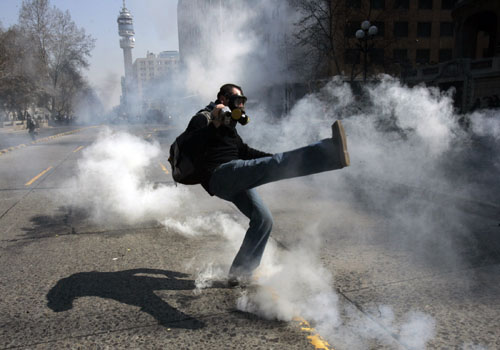 A demonstrator kicks a canister of tear gas during a rally in Santiago, Chile on Wednesday.
