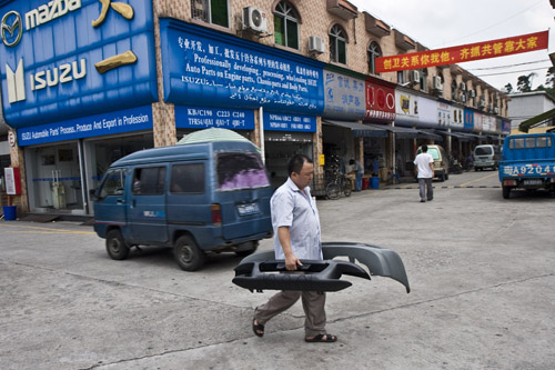 A man is seen carrying automotive spare parts at a market, in Guangzhou, China in this July 7 file photo.
