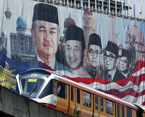 A Light Rail Transit passenger train passes by a banner of Malaysia's past and present ministers at downtown Kuala Lumpur.