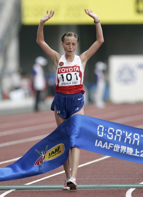 Russia's Olga Kaniskina waves as she crosses the finish line in Osaka, Japan yesterday.