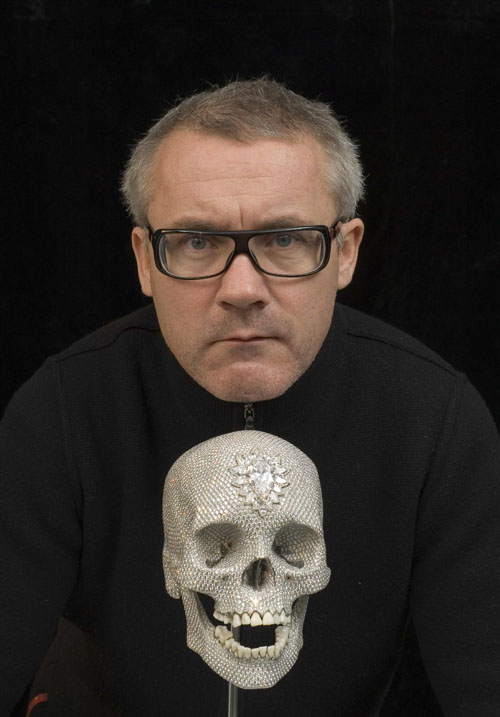 British artist Damien Hirst poses with a diamond-encrusted platinum skull in this undated handout file photograph released in London, England on June ...