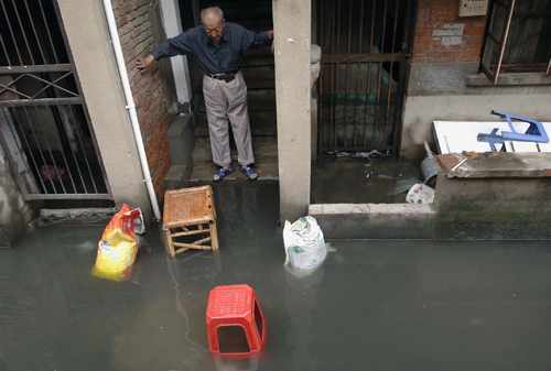 A man stands beside a flooded passageway in Hefei, Anhui province, China yesterday after Typhoon Wipha swept through the region.