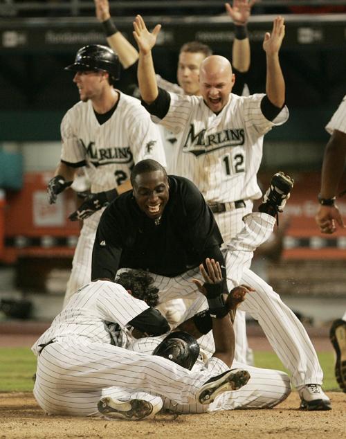 Florida Marlins jump on Hanley Ramirez after he scored the winning run in Miami, Florida on Thursday.
