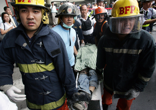 Rescuers carry a victim following a powerful explosion at the busy Glorietta Shopping Mall in Makati City, east of Manila, Philippines Friday.