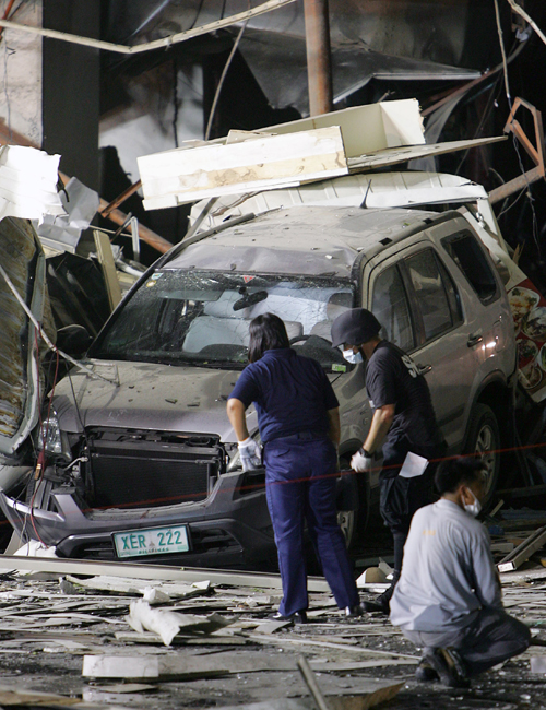 Police investigators search the ground for evidence near damaged vehicles after an explosion on Friday in Manila's financial district of Makati, Phil...