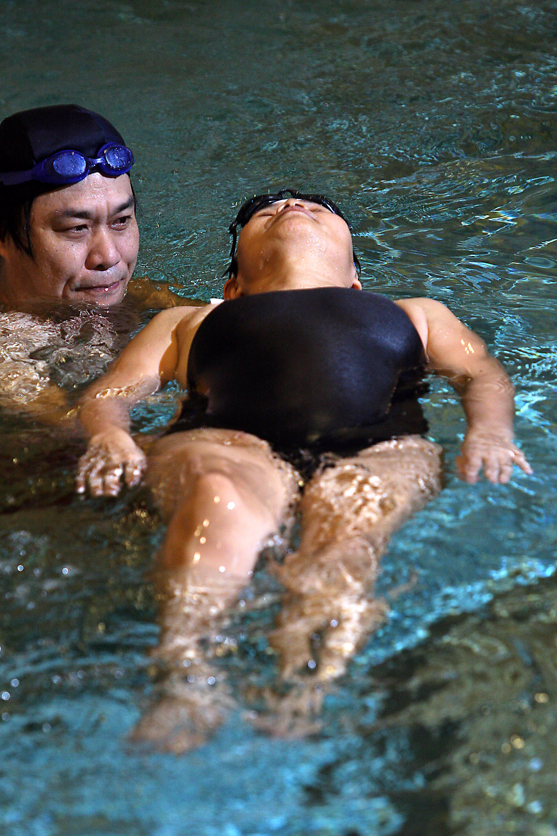 A husband guides his wife, who is in the last stages of colon cancer, in the pool during a charity event held at the Taipei Medical University Hospita...