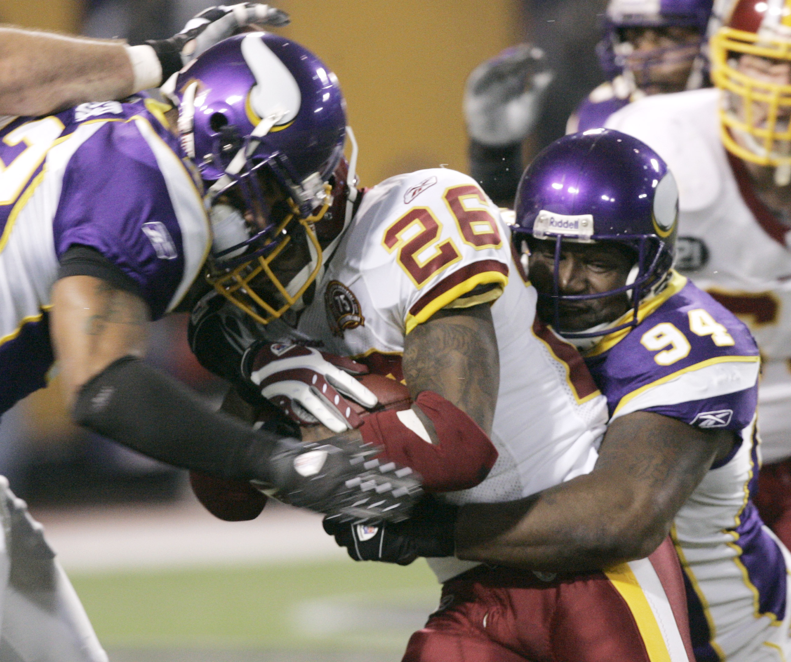 The Minnesota Vikings' Darren Sharper, left, and Pat Williams, right, bring down Washington Redskins running back Clinton Portis for a loss in the fir...