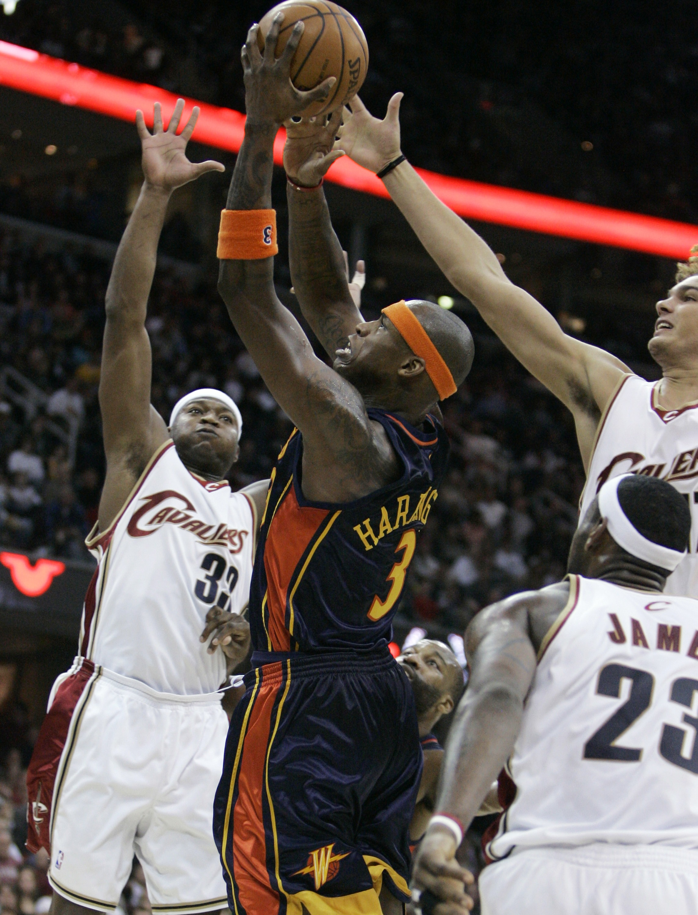 The Golden State Warriors' Al Harrington, center, goes to the basket against the Cleveland Cavaliers' Devin Brown, left, Anderson Varejao, background ...