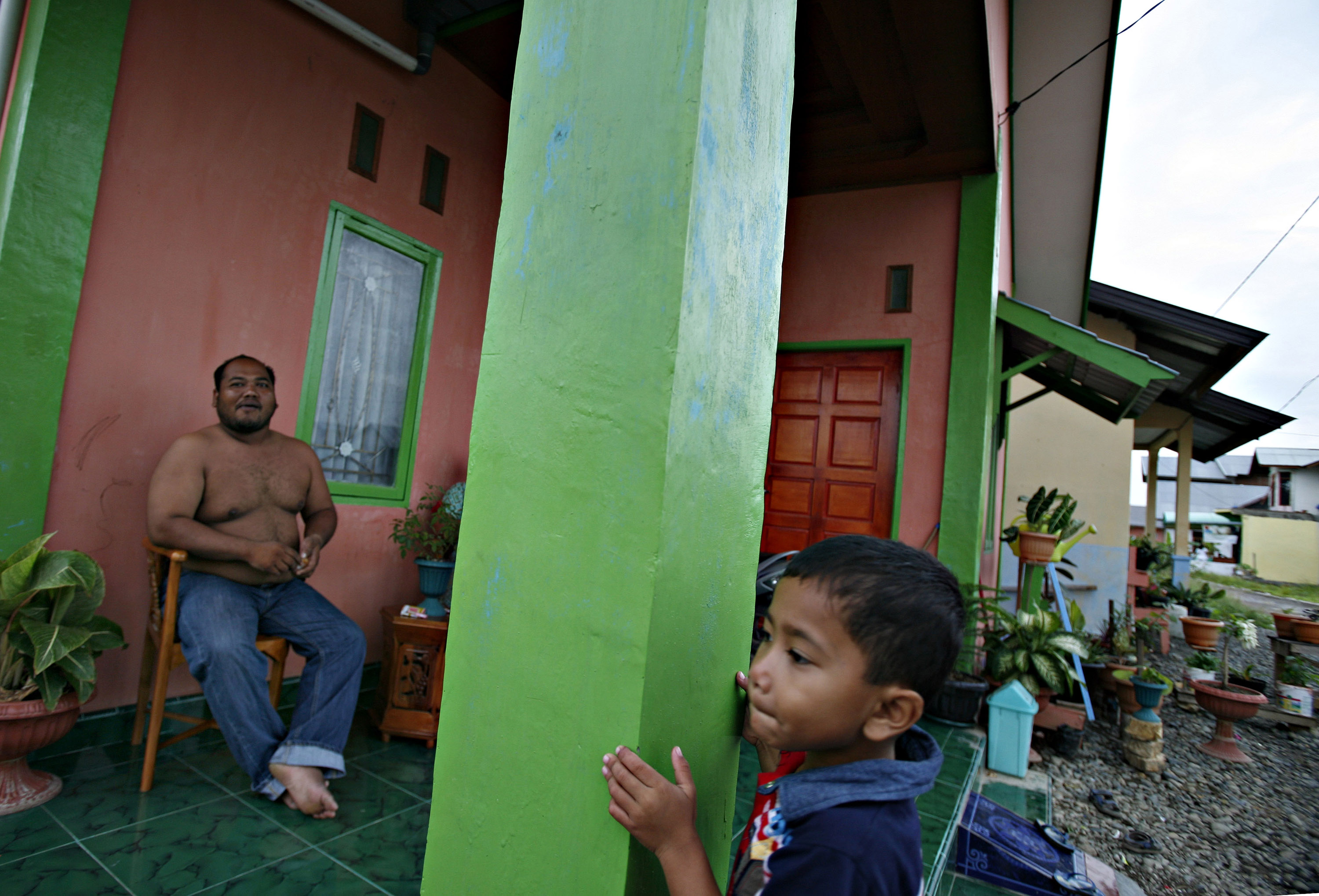 An Acehnese boy plays, as his father watches, in their new home built by an aid organization in Banda Aceh, Indonesia in this November 30 photo.