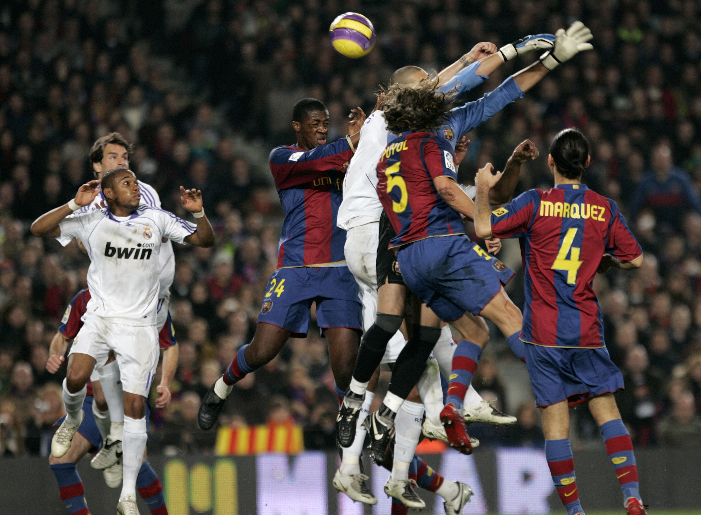 Real Madrid's Sergio Ramos (obscured, center) jumps for the ball against Barcelona's goalkeeper Victor Valdes during their Spanish first division socc...