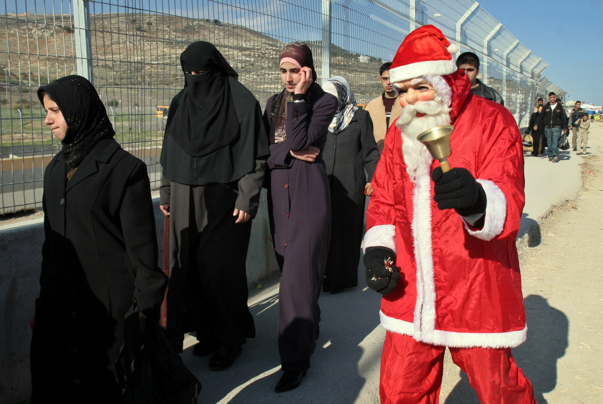 A Palestinian Santa Claus rings his bell as he walks near the Hawara checkpoint in the West Bank town of Nablus, Monday. Gloom was banished from Chris...