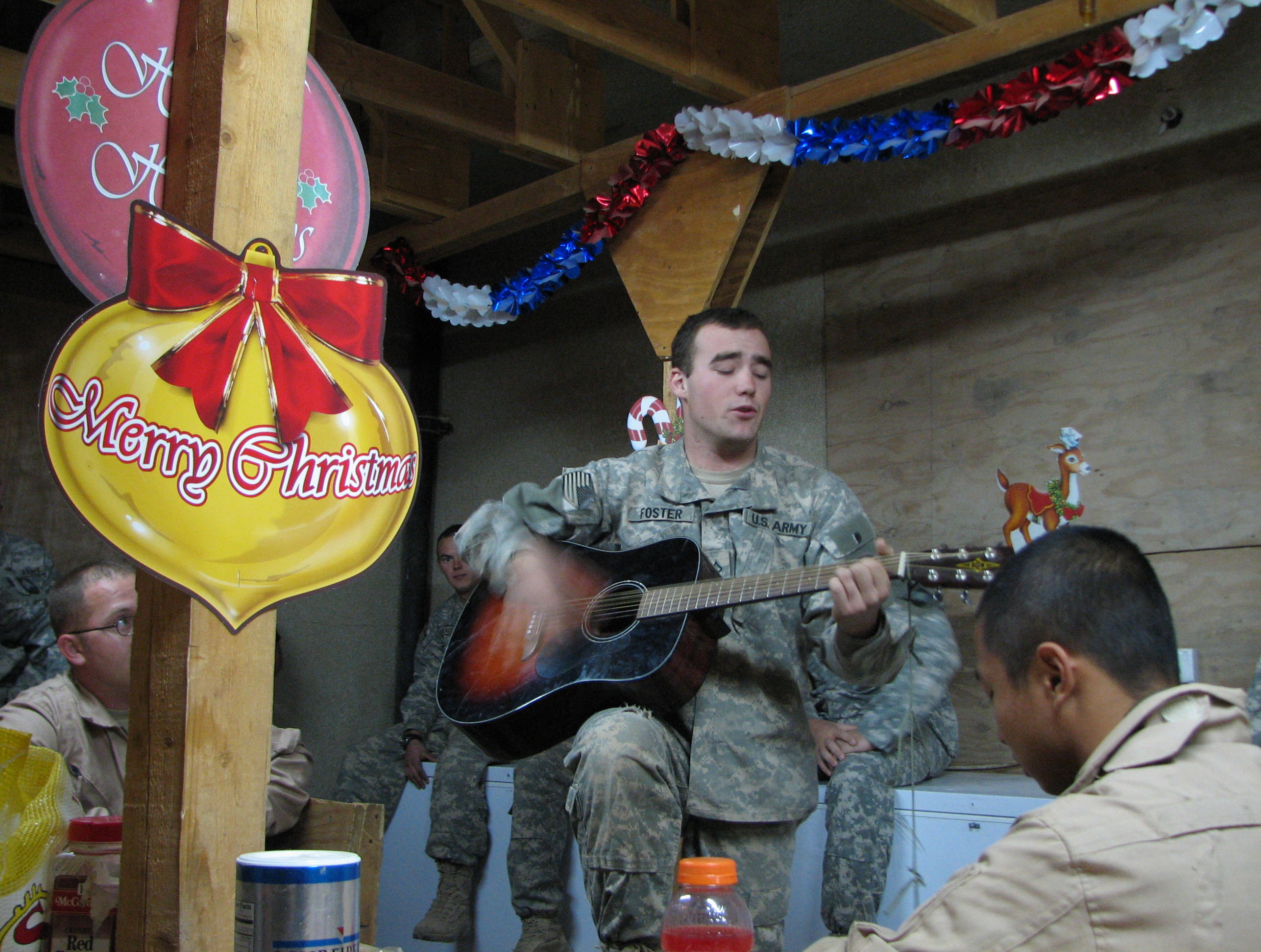Private First Class Dan Foster, of Costa Mesa, California sings during a Christmas skit competition at Patrol Base Warrior Keep in Baghdad, Iraq. The ...
