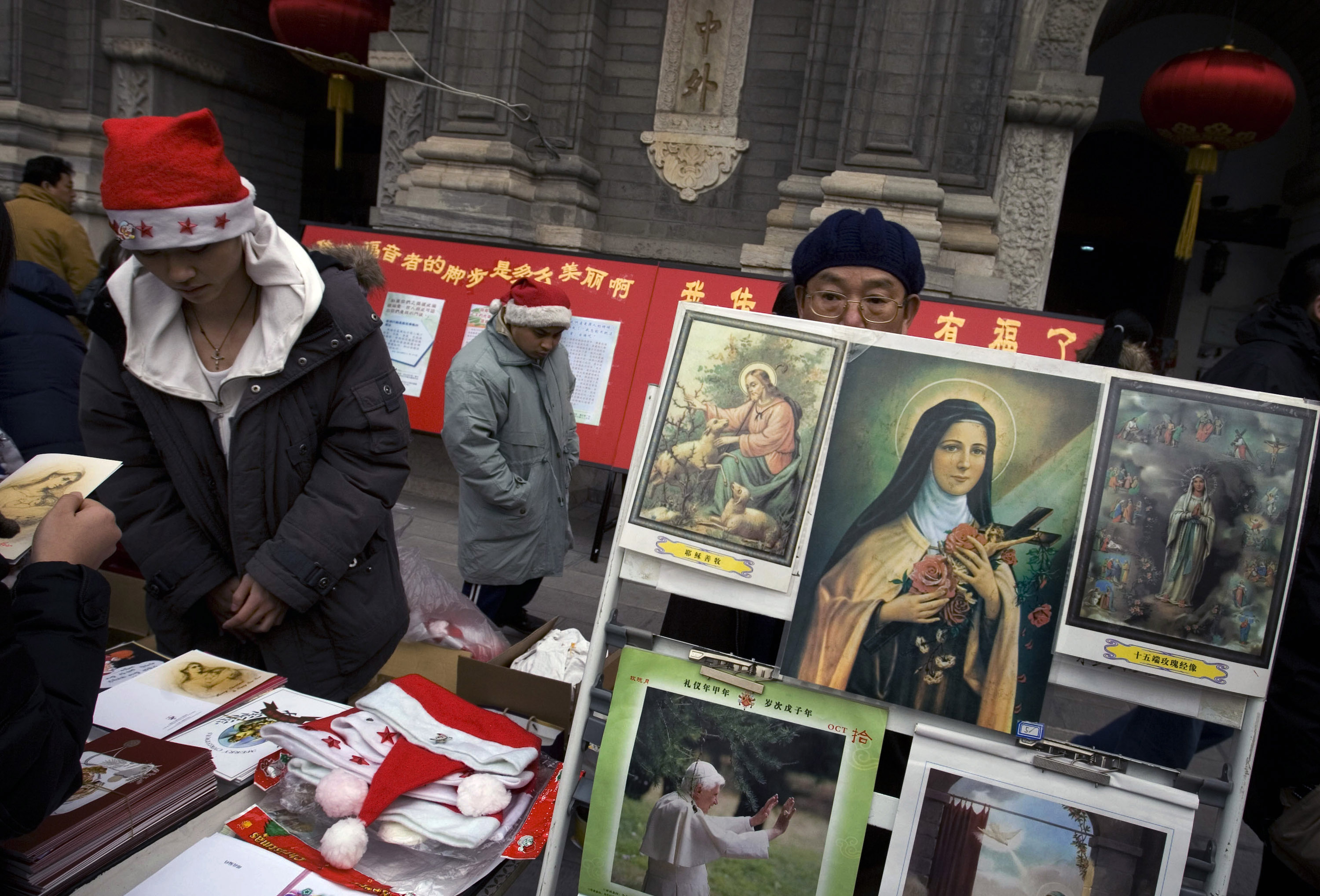 Church workers sell religious memorabilia outside the church on Christmas Eve in Beijing Monday.
