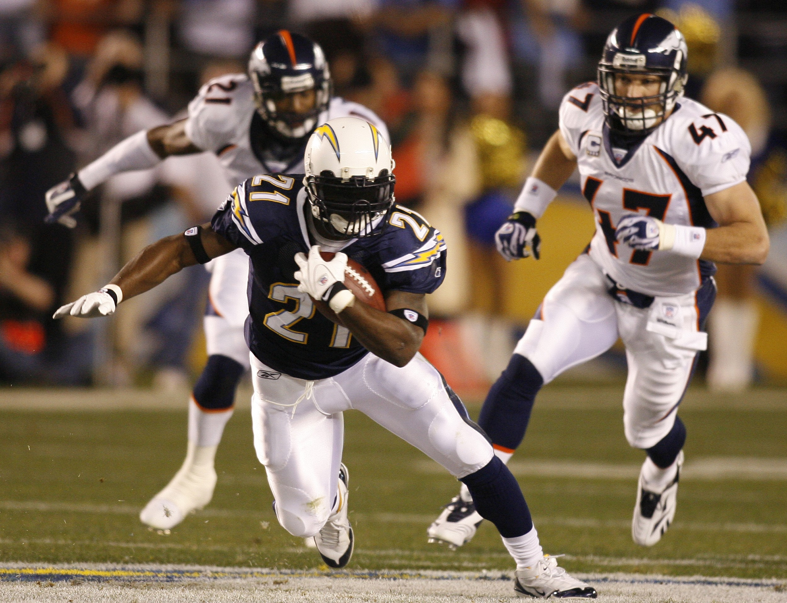 San Diego Chargers running back LaDainian Tomlinson (21) leaves Denver Broncos' John Lynch, right, and Hamza Abdullah behind while running for a first...