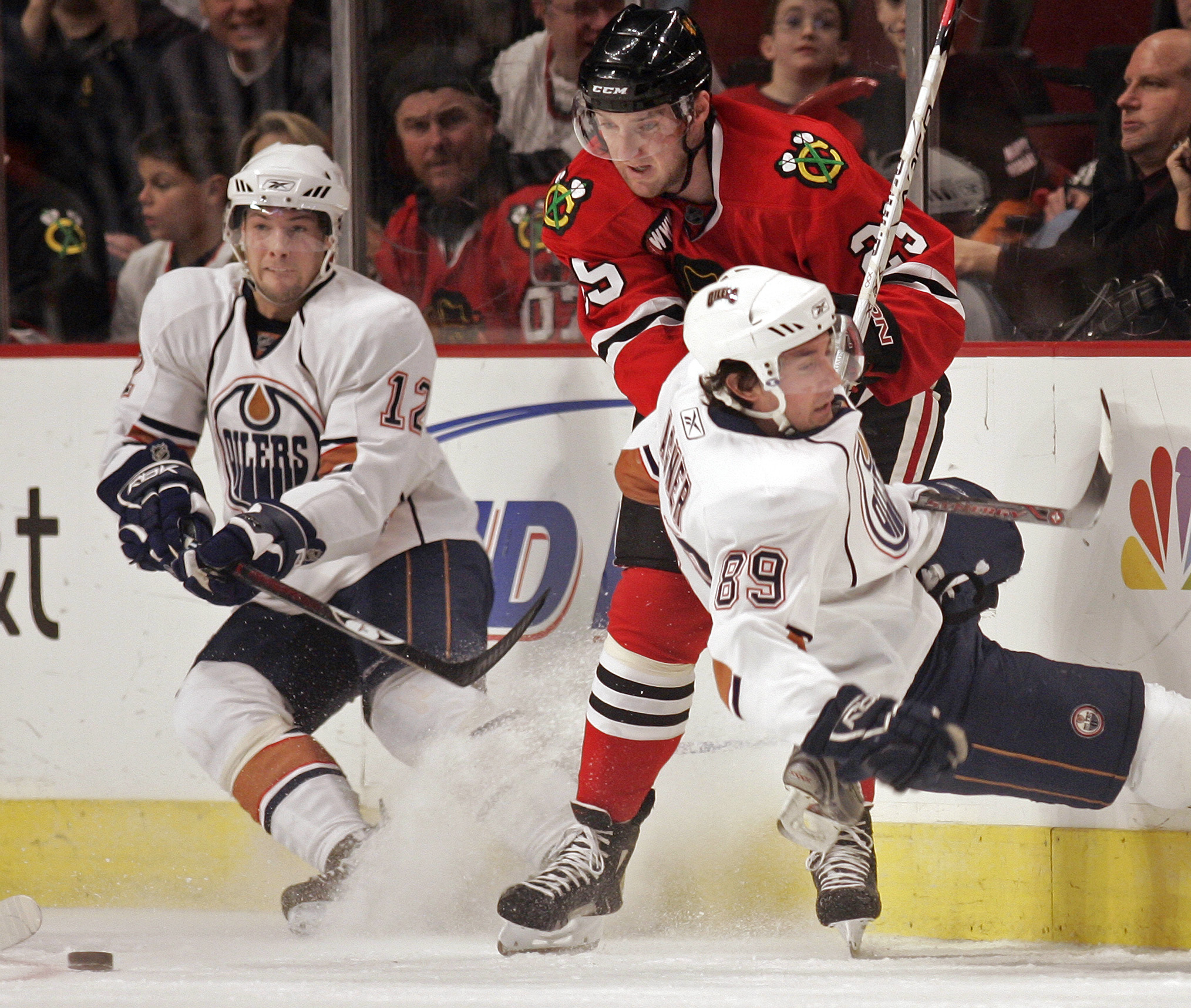 Edmonton Oilers' Robert Nilsson (12) looks to pass the puck as teammate Sam Gagner (89) gets knocked down by Chicago Blackhawks' Cam Barker during the...