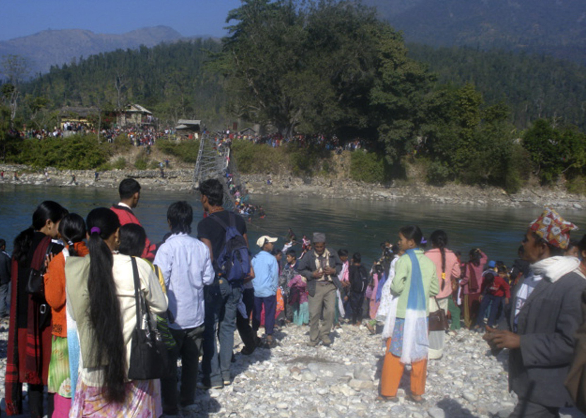 Relatives and rescuers look on as a footbridge over River Bheri collapses in Chunchu village, about 500 kilometers west of Katmandu, Nepal on Wednesda...