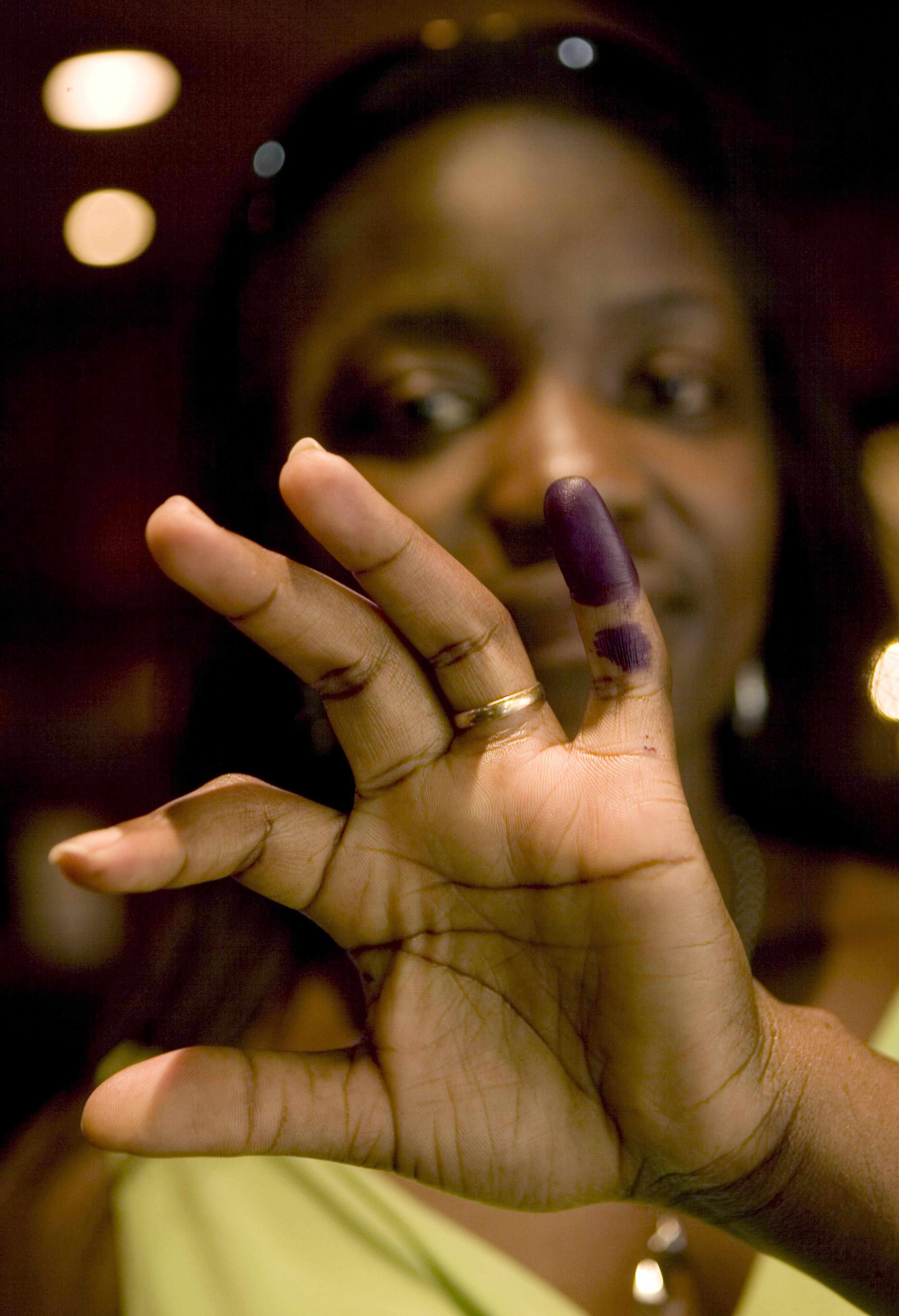 A Kenyan woman shows her finger dipped in ink as proof of participating in the presidential election yesterday.