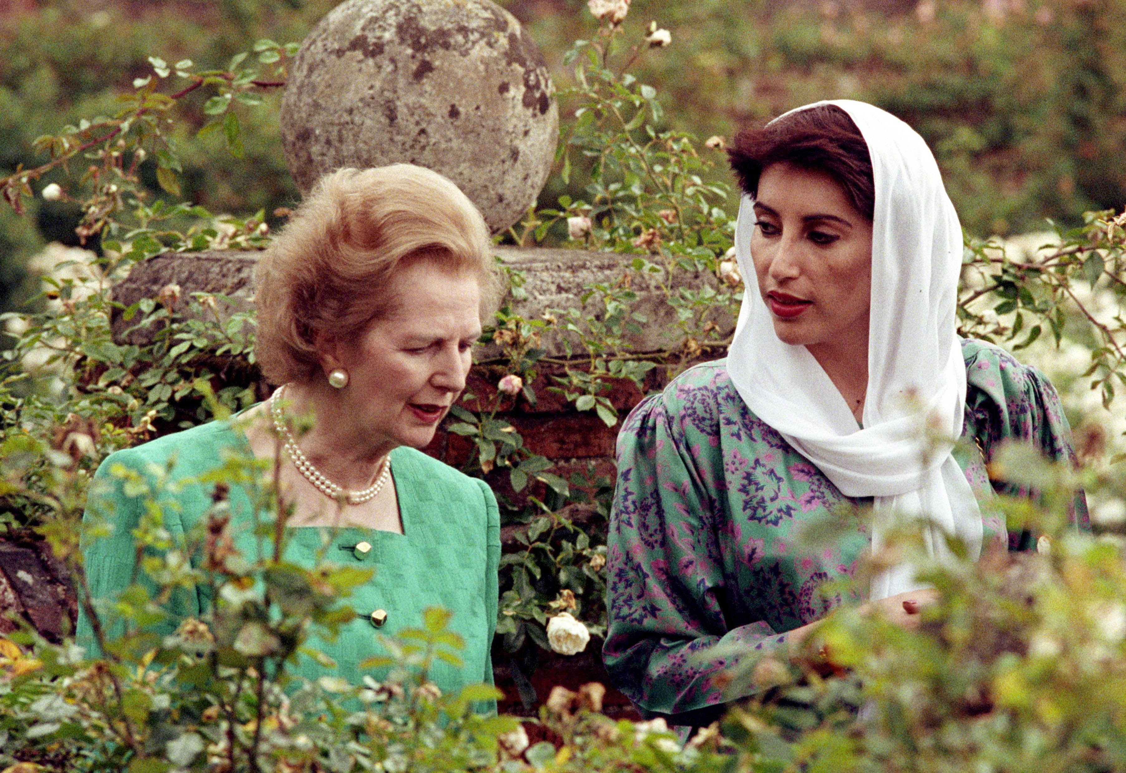 Pakistan's opposition leader Benazir Bhutto walks with then British Prime Minister Margaret Thatcher in the rose garden at Chequers, Thatcher's countr...
