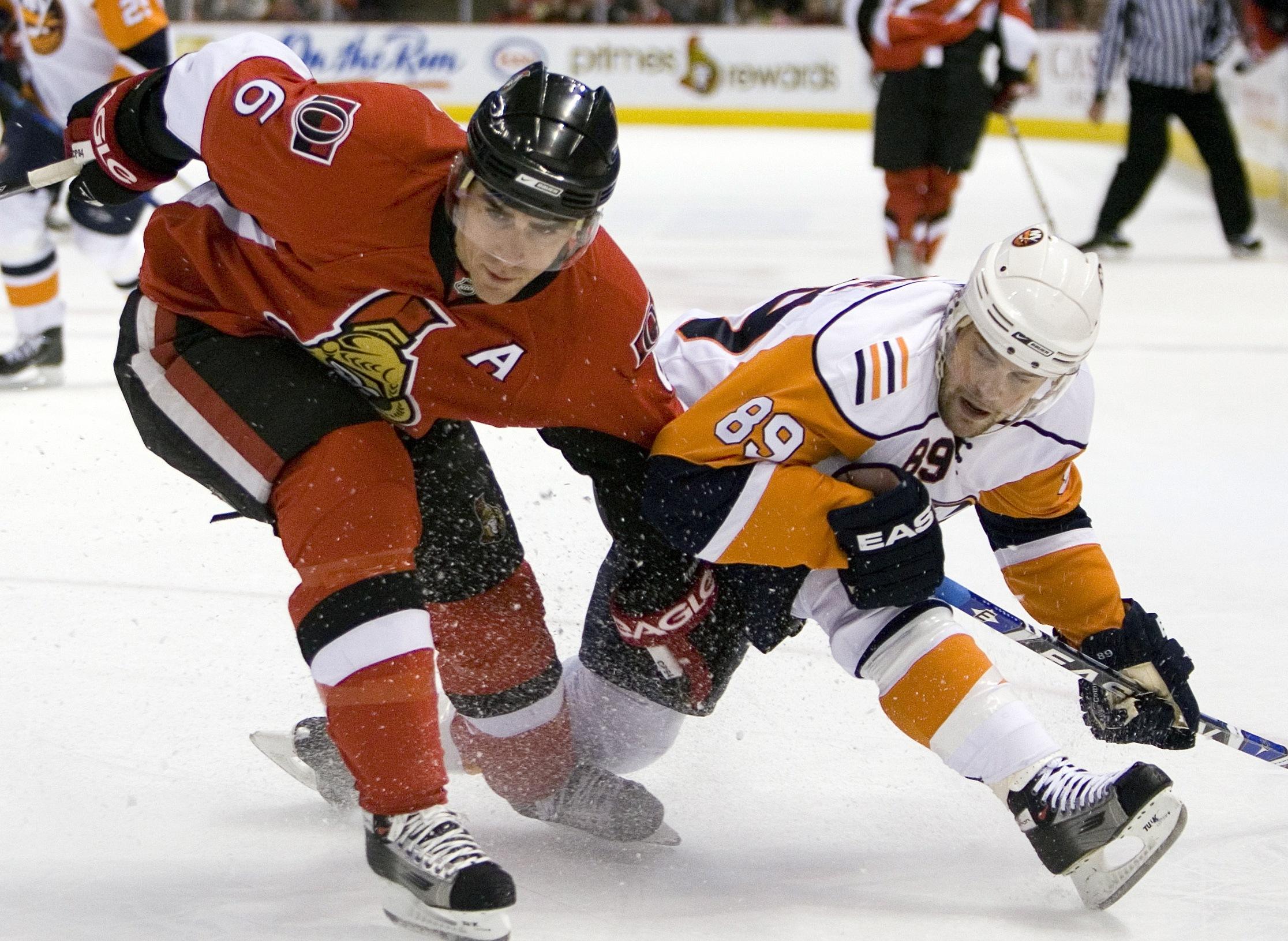 New York Islanders' Mike Comrie, right, and Ottawa Senators' Wade Redden get tangled up during first period NHL hockey action in Ottawa, Canada on Thu...