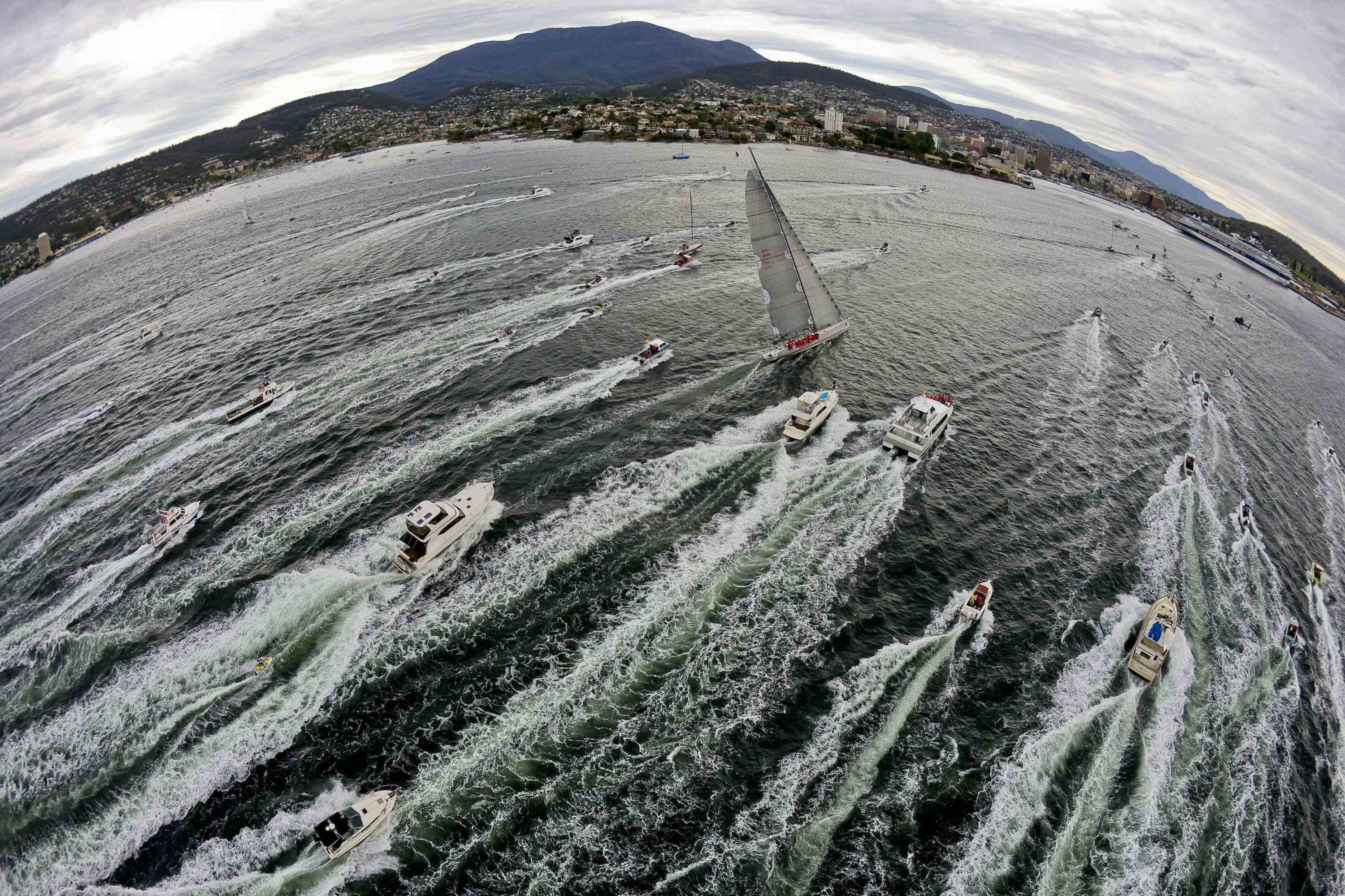 Australian yacht Wild Oats XI crosses the finish line in Hobart to take line honors during the annual Sydney to Hobart yacht race yesterday.