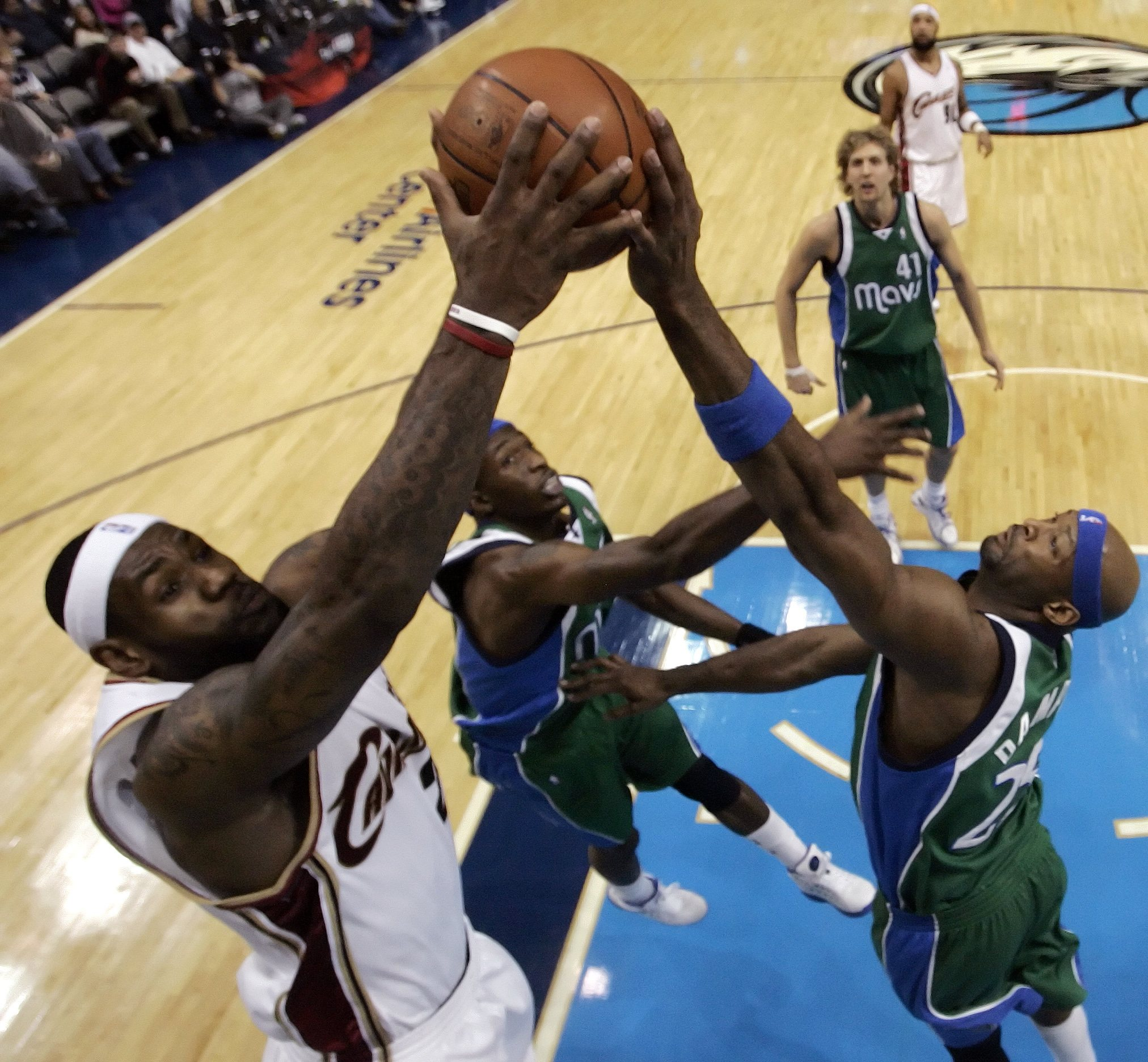 Cleveland Cavaliers forward LeBron James, left, goes up for a shot as Dallas Mavericks center Erick Dampier, right, goes for the block and forward Jos...