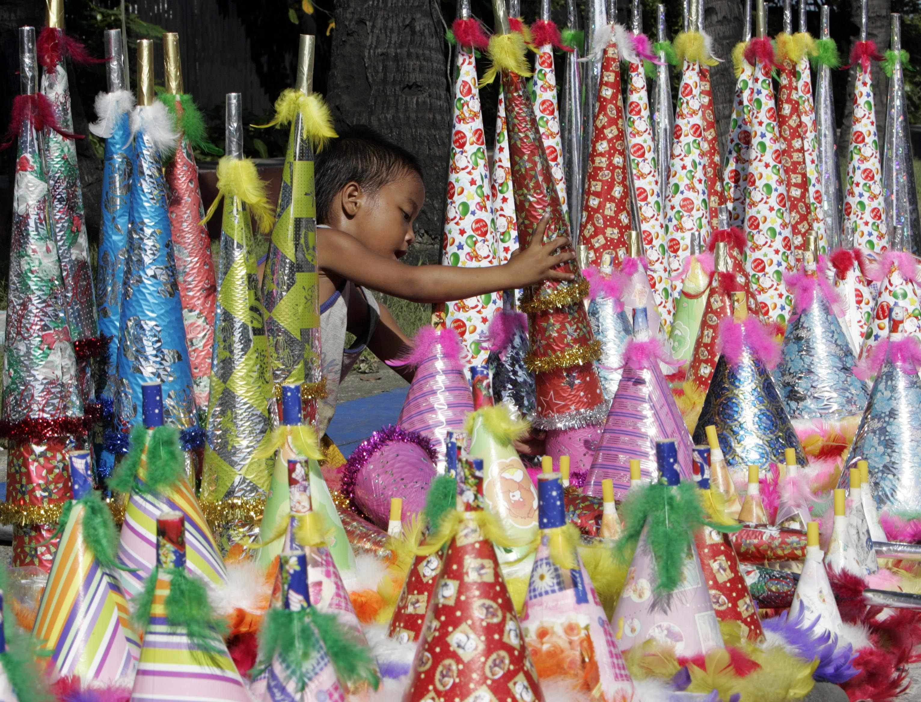 A boy stacks up blow horns made of cardboard and plastic sold by his mother for 30 cents per piece along a sidewalk in preparation for New Year celebr...
