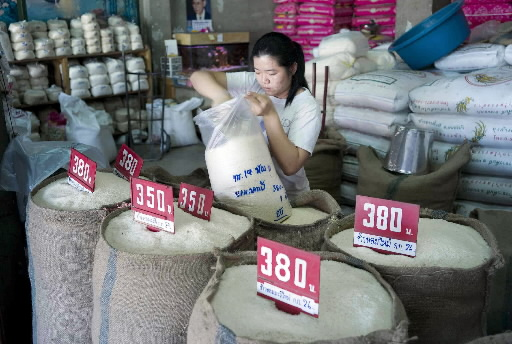 A worker measures rice at a distribution point in Bangkok, Thailand on Saturday. Thailand's economy grew at the fastest pace in the last three months ...