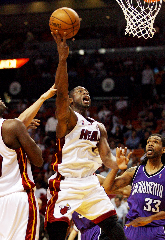 Miami Heat's Dwyane Wade, center, drives and scores against Sacramento Kings' Mikki Moore during their NBA basketball game in Miami, Florida on Tuesda...