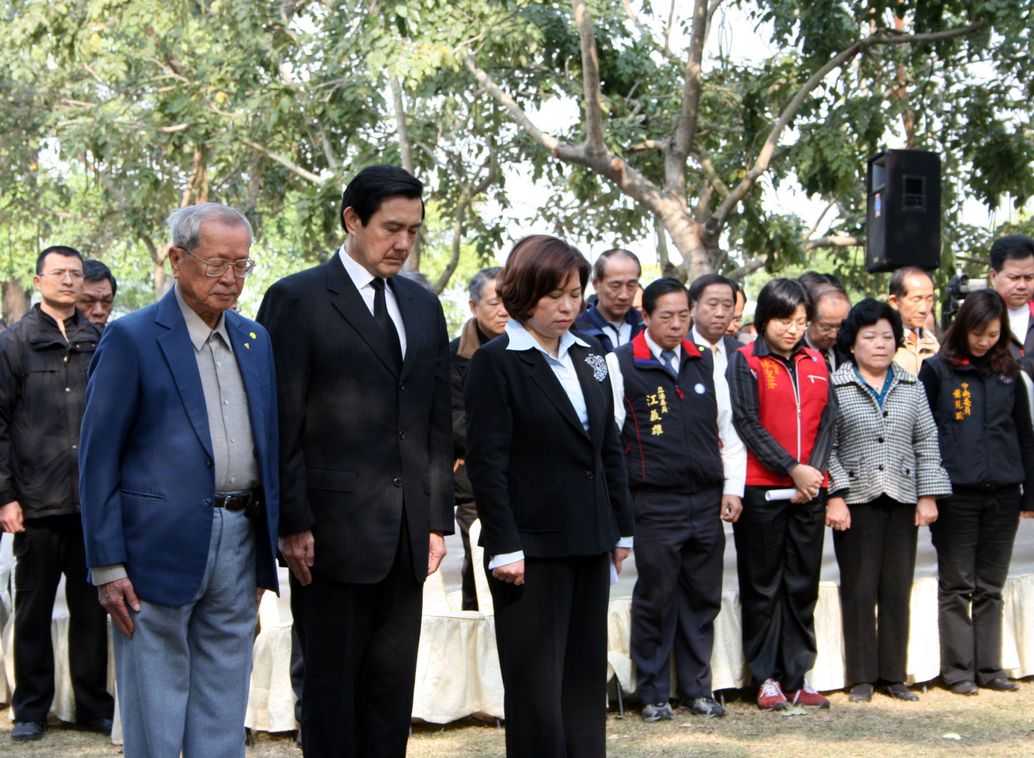 Kuomintang presidential candidate Ma Ying-jeou, left, joins family members of victims of the 228 Incident at a ceremony at 228 Memorial Park in Chiayi...