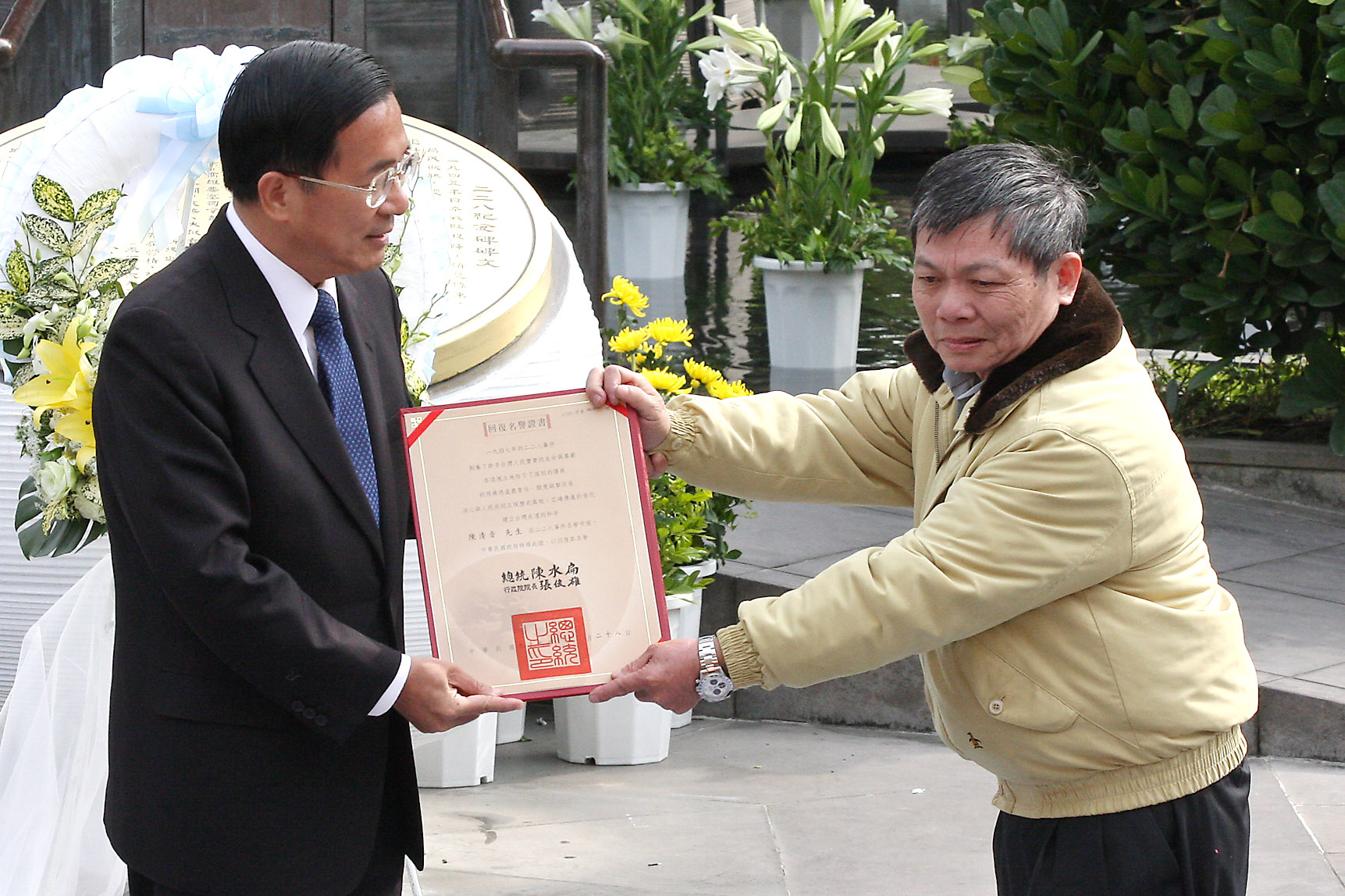 President Chen Shui-bian, left, presents a certificate to 228 victim Chen Chin-yin to formally clear his name, during a ceremony held in Taipei yester...