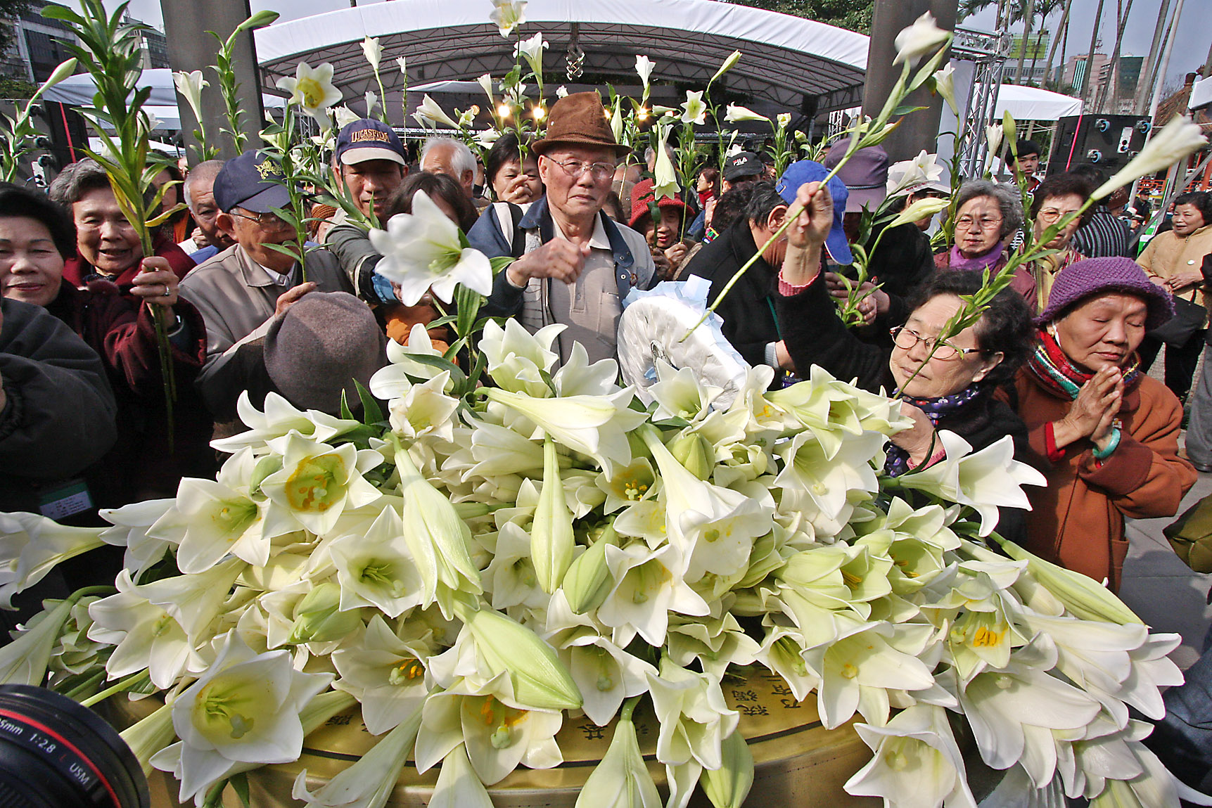 People place lilies at 228 Memorial Park to commemorate the victims of the 