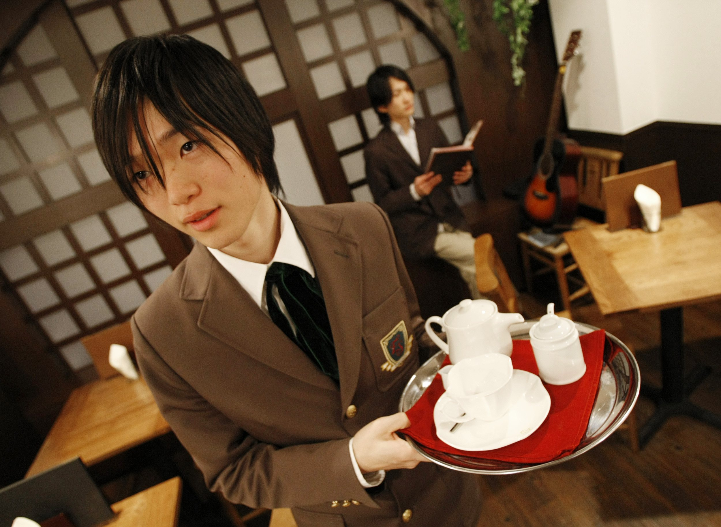 Waiters Yuta Asami, left, and Ritsuki Sunomiya, dressed as a schoolboy and a schoolteacher, respectively, are seen working at Edelstein cafe in Tokyo,...